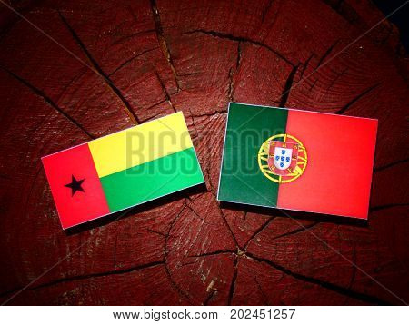 Guinea Bissau Flag With Portuguese Flag On A Tree Stump Isolated