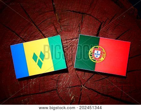 Saint Vincent And The Grenadines Flag With Portuguese Flag On A Tree Stump Isolated