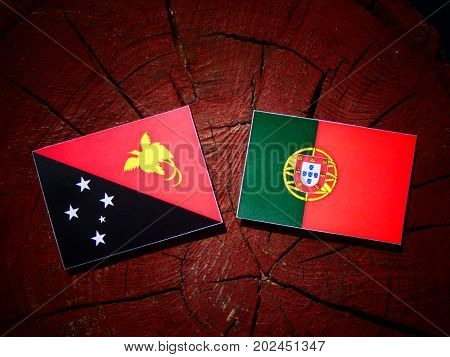 Papua New Guinea Flag With Portuguese Flag On A Tree Stump Isolated