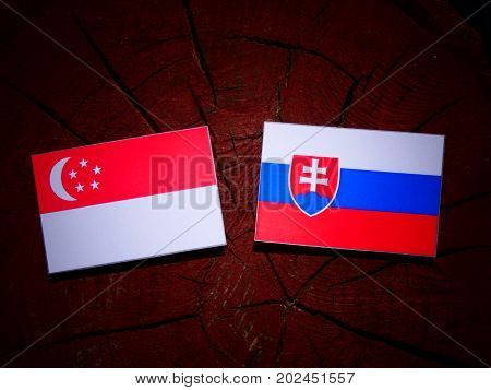 Singaporean Flag With Slovakian Flag On A Tree Stump Isolated