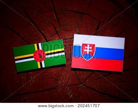 Dominica Flag With Slovakian Flag On A Tree Stump Isolated
