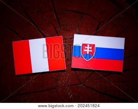 Peruvian Flag With Slovakian Flag On A Tree Stump Isolated
