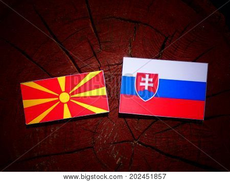 Macedonian Flag With Slovakian Flag On A Tree Stump Isolated