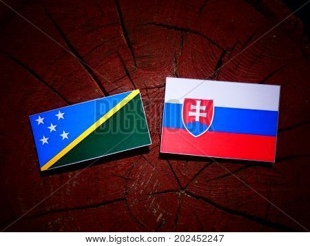 Solomon Islands Flag With Slovakian Flag On A Tree Stump Isolated