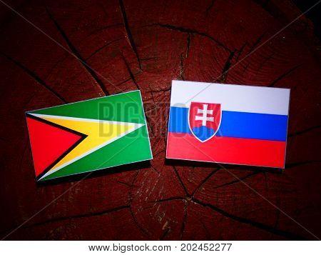 Guyana Flag With Slovakian Flag On A Tree Stump Isolated