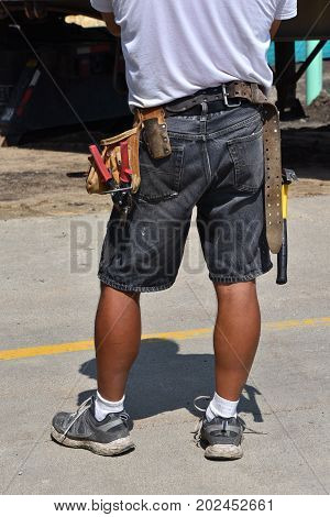 An identified  wood carpenter stands with work tools attached to his belt