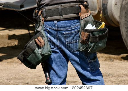 An unidentified  wood carpenter stands with work tools attached to his belt