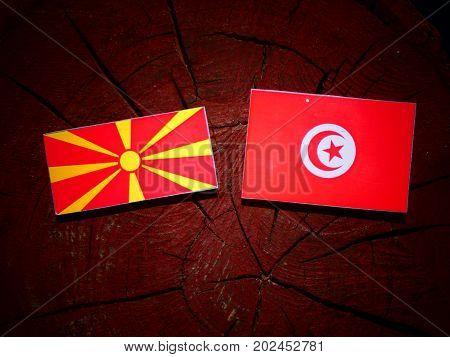 Macedonian Flag With Tunisian Flag On A Tree Stump Isolated