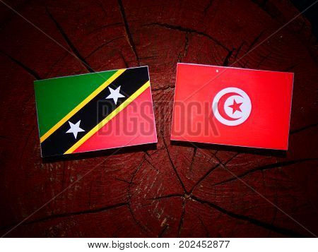 Saint Kitts And Nevis Flag With Tunisian Flag On A Tree Stump Isolated