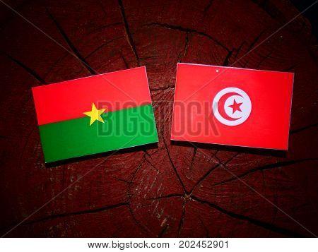 Burkina Faso Flag With Tunisian Flag On A Tree Stump Isolated