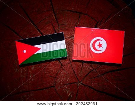 Jordanian Flag With Tunisian Flag On A Tree Stump Isolated