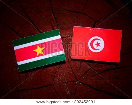 Suriname Flag With Tunisian Flag On A Tree Stump Isolated