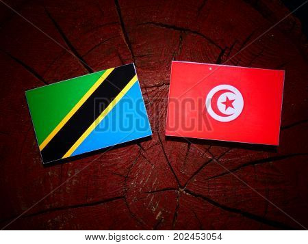 Tanzanian Flag With Tunisian Flag On A Tree Stump Isolated
