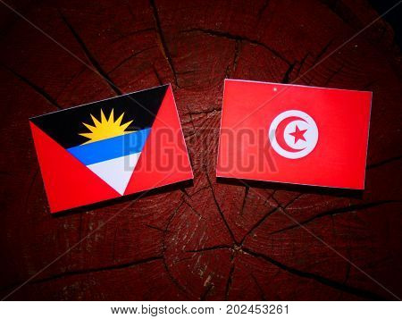 Antigua And Barbuda Flag With Tunisian Flag On A Tree Stump Isolated