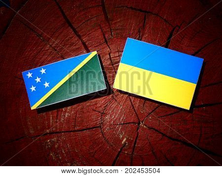Solomon Islands Flag With Ukrainian Flag On A Tree Stump Isolated