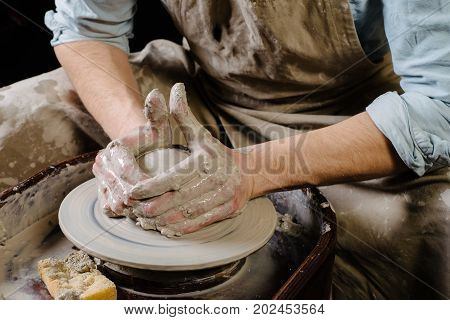 pottery workshop ceramics art concept - closeup on male hands sculpt new utensil with a tools and water man's fingers work with potter wheel and raw fireclay front close view