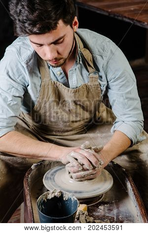 pottery workshop ceramics art concept - man working on potter's wheel with raw clay with hands a male brunette sculpt a utensils near wooden table with tools master in apron and a shirt