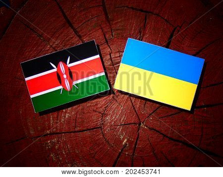 Kenyan Flag With Ukrainian Flag On A Tree Stump Isolated