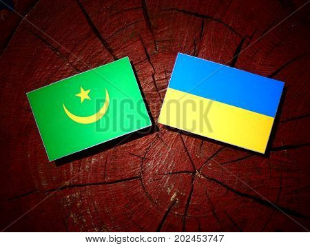 Mauritania Flag With Ukrainian Flag On A Tree Stump Isolated