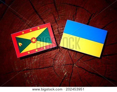 Grenada Flag With Ukrainian Flag On A Tree Stump Isolated