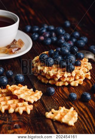 Cup of Tea with Blueberries on the Top of the Waffles Stack. Other Berries and Broken Waffle Scattered on Wooden Background.