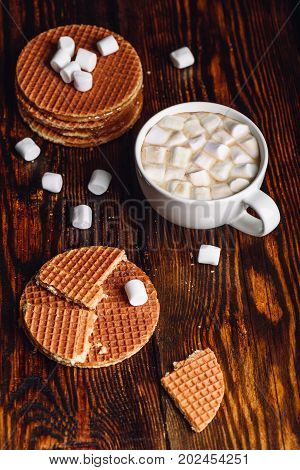 Homemade Dutch Waffles with Broken One with White Cup of Cocoa with Marshmallow and Waffle Stack. Vertical Orientation.