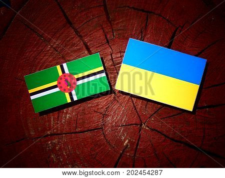 Dominica Flag With Ukrainian Flag On A Tree Stump Isolated