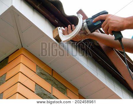 Installing Holder rain gutter system on the roof. Rain Gutter Holder Installation