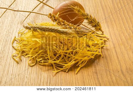 Pasta, eggs and ears of wheat placed on oak wooden plate