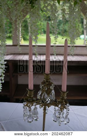 Beautiful wedding decoration. Candlestick together in pink candles.