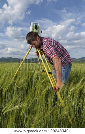 Land surveyor in agriculture field of wheat