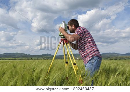 Young land surveyor in a wheat field