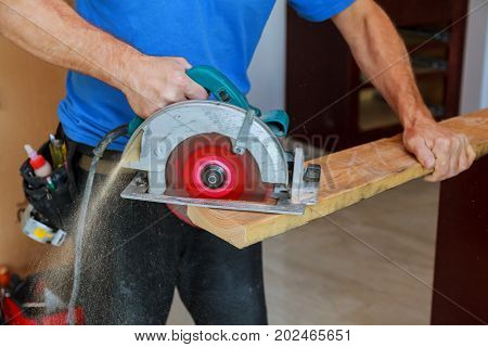 Man using circular saw Close up electric saw to sawing wood board solf focus.