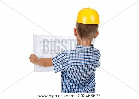 Cute serious builder boy is reading a building paper plan, turned back, isolated on white background