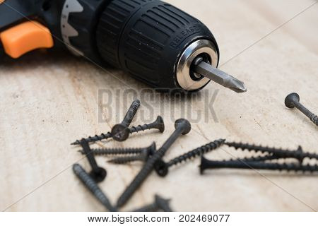 Diy tools concept. Many screws and a screwdriver on a pine board. Cordless drill with screws DIY background.