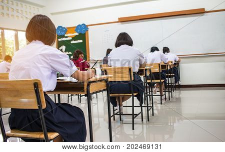 Asian School students in uniform taking examination and writing answer sheet in classroom educational school view of having exams in class on seat rows Education system tests concept of Thailand