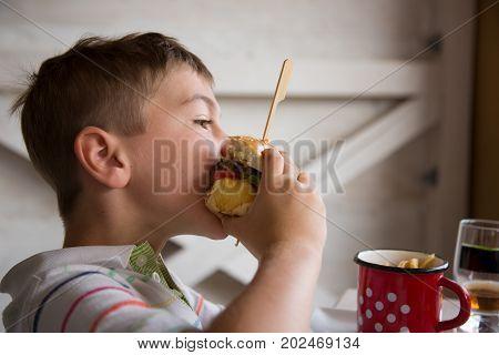 Young boy eats big hamburger and chips