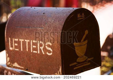 Old rusty brown mailbox with letterbox text, in worn condition, outdoor