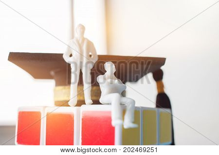 Two Miniature figurine sitting on rubik puzzle with Graduation cap Rubik's Cube is 3D combination puzzle invented Education international Concept