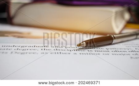 Blue metal pen on letter-writing paper book with letter about postgraduate or undergraduate degree in college or school with image of of hands writing article near textbook concept of education