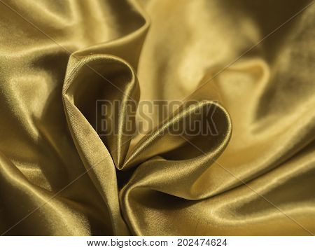 golden heart shaped from atlas velour textile fabric - abstract love background