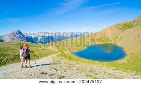 Couple Of Hiker On The Mountain Top Looking At Blue Lake And Mountain Peaks. Summer Adventures On Th