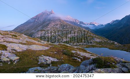 High Altitude Alpine Lake In Idyllic Land With Majestic Rocky Mountain Peaks. Long Exposure At Dusk.