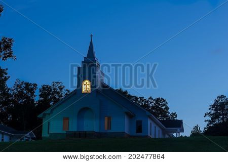 A rural church on the hill bathed in the blue afterglow of the sunset.