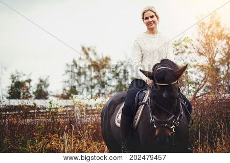 Smiling Young Woman Sitting On Her Horse In A Pasture