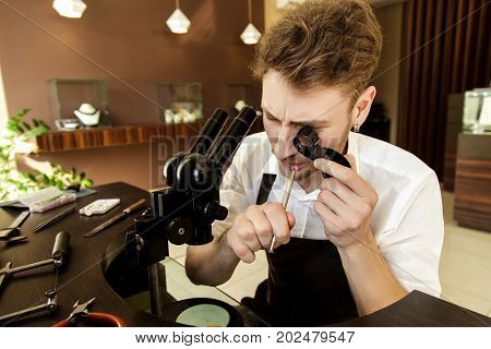 The Jeweler Examines The Gem Under The Magnifying Glass