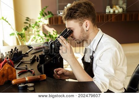 A Jeweler Carefully Examines The Stone To Create A Ring Through A Microscope