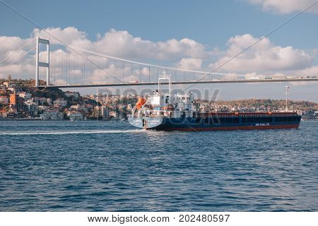 ISTANBUL TURKEY - NOVEMBER 17 2013: Seascape of Bosphorus. View of the tanker ship floating on the water and Fatih Sultan Mehmet Bridge. Gulls fly in the sky. Istanbul Turkey.