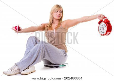 Diet fitness slimming loosing weight concept. Curvy woman holding apple measuring tape and big old fashioned clock sitting on weighing machine