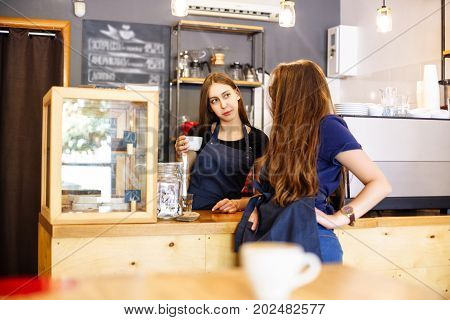 Two Young Women Barista At A Bar Counter